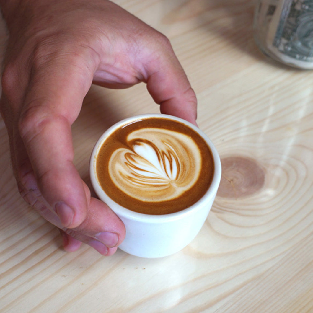 Hand holding a cup of coffee.