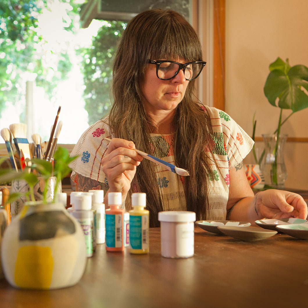 Jennifer at work painting her ceramic pieces.