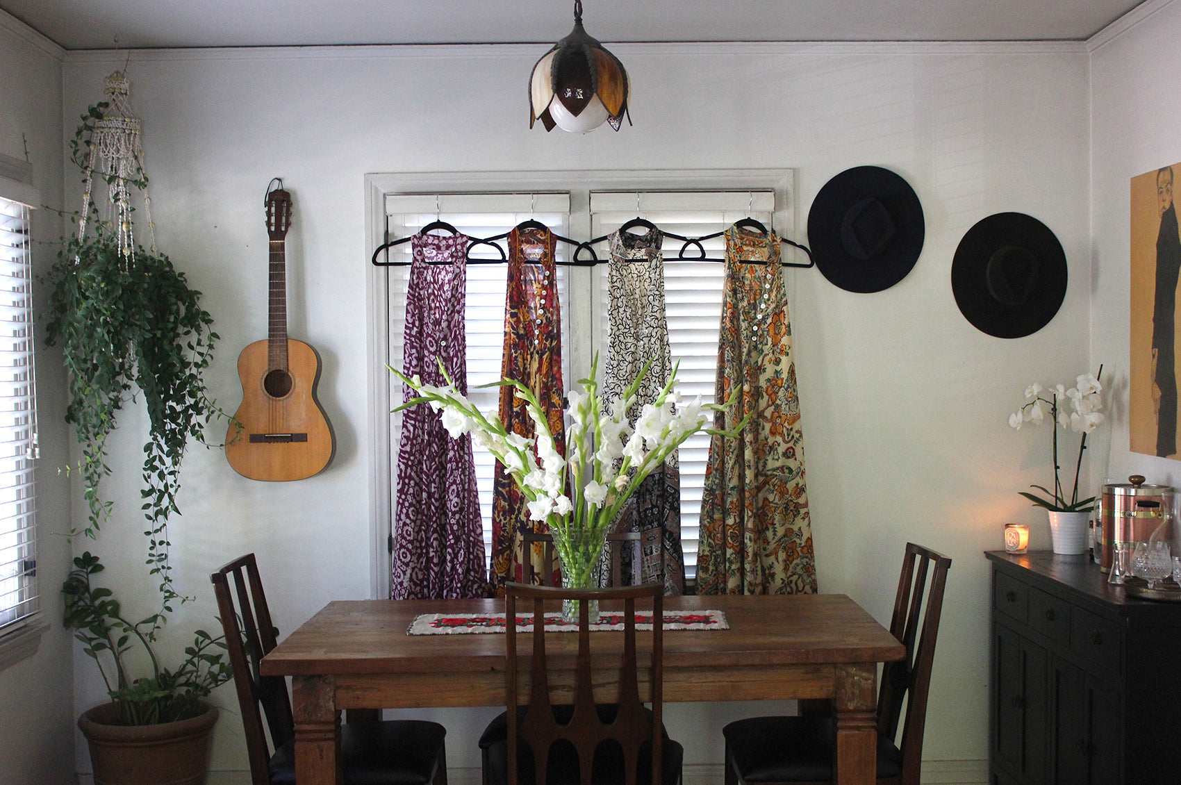 Four of Roxana's dresses hanging in front of a window surrounded by hanging guitars and hats.