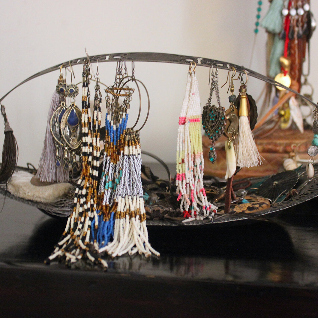 Metal basket filled with earrings and other jewelry.