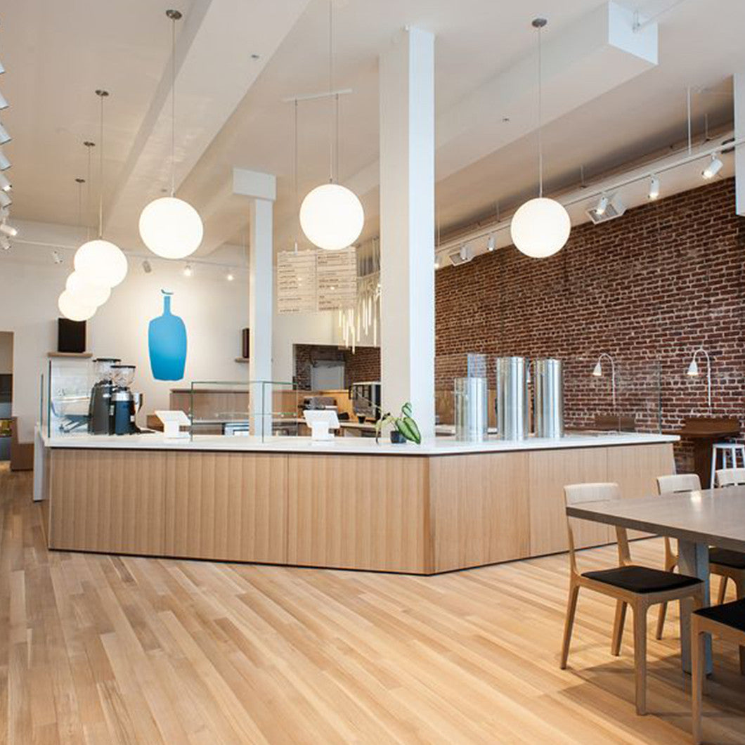 Beatuiful wooden flooring and brick wall adorn the interior of the Blue Bottle cafe.