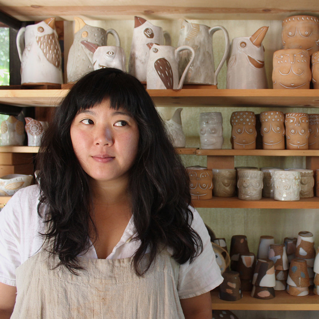 Image of Linda standing in front of her creations.