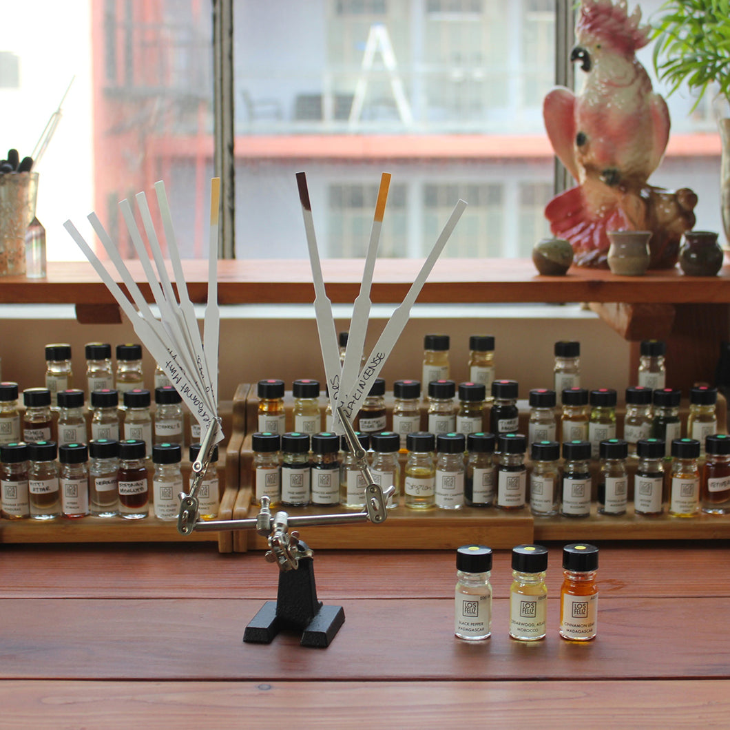 Oils and fragrance sticks on display on a wooden table.