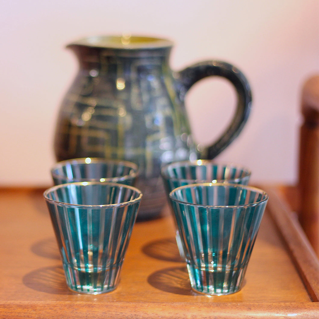 Blue and clear shot glasses and ceramic pitcher.