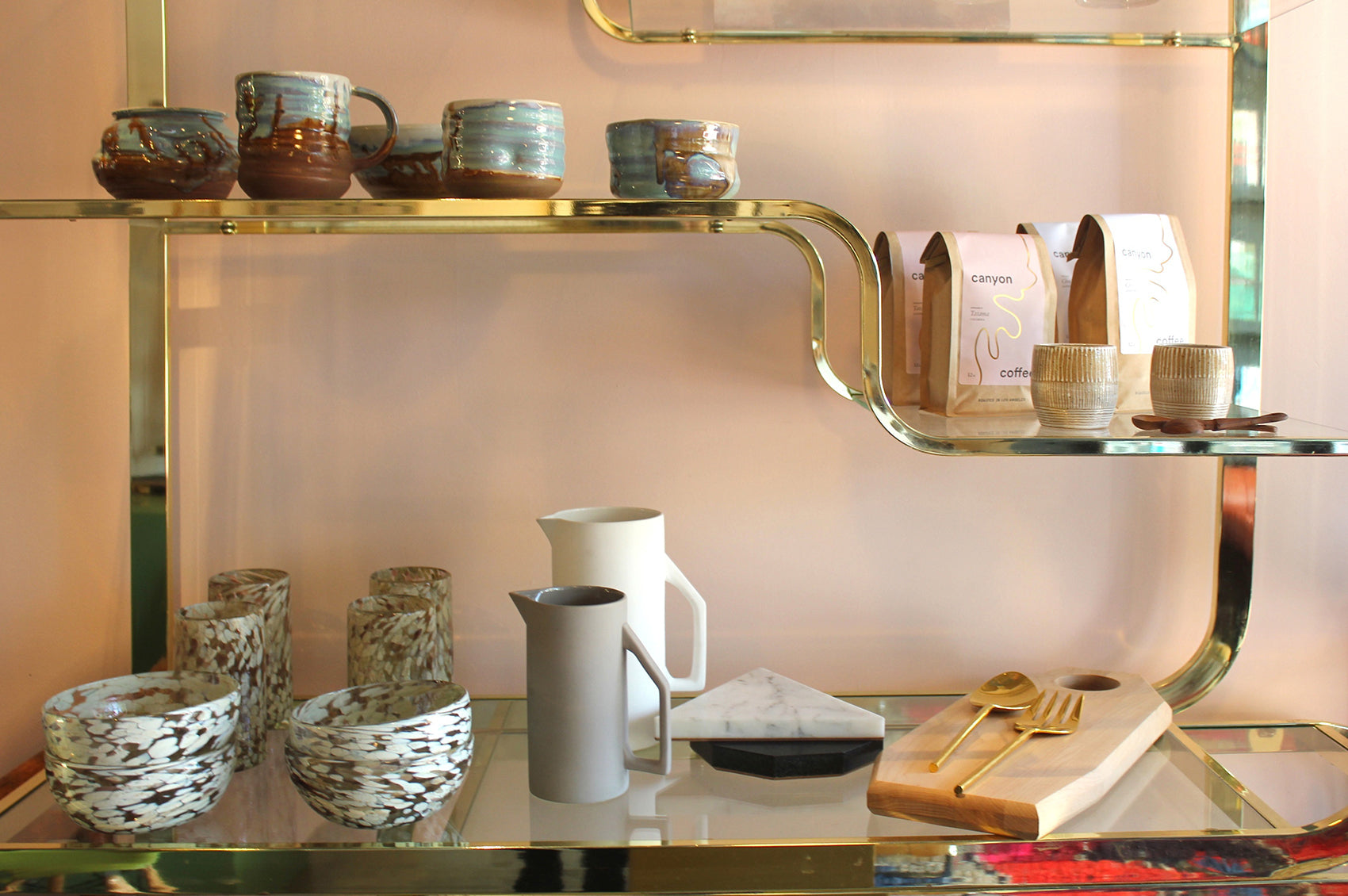 Ceramic bowls, mugs, cups, pitchers, and coffee line a few of the shelves in Night Palm.