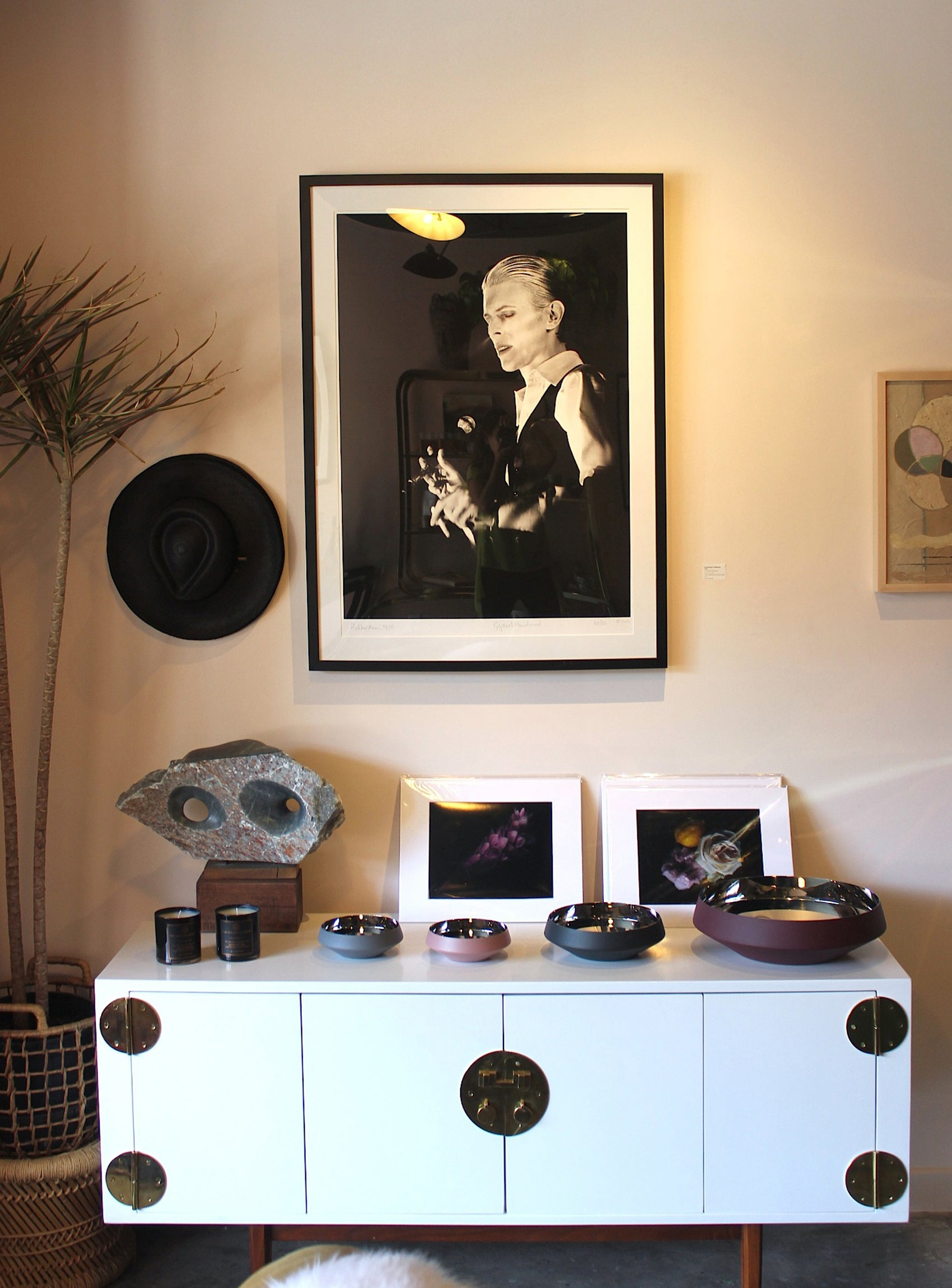 A framed photo of David Bowie hangs above a white table topped with different sized bowls.