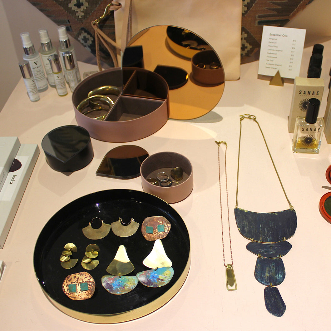 A table displays jewelry and bath and beauty products sold at Night Palm.
