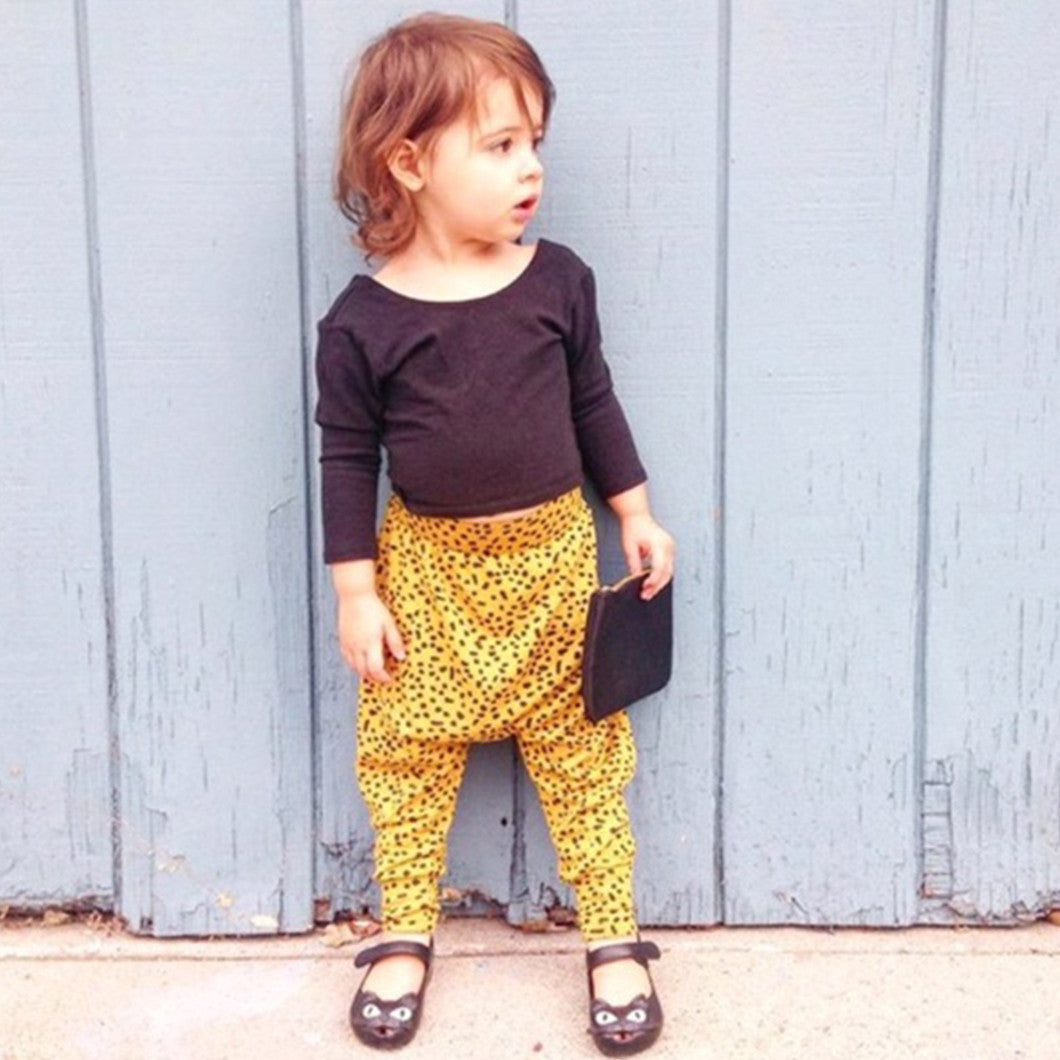 Michelle's daughter, Violet, wearing yellow harem pants and a black long-sleeved top.