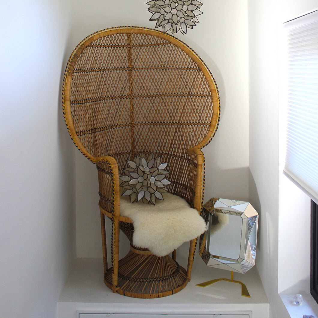 Intricately woven chair adorned with a lamb's wool throw and geometric figures.