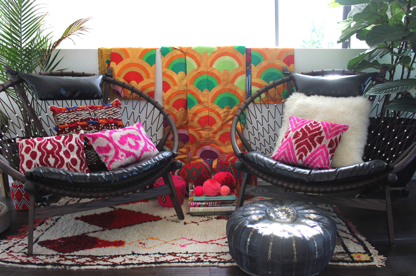 Rosa's sitting area decorated with colorful pillows, carpet, and wall hangings.