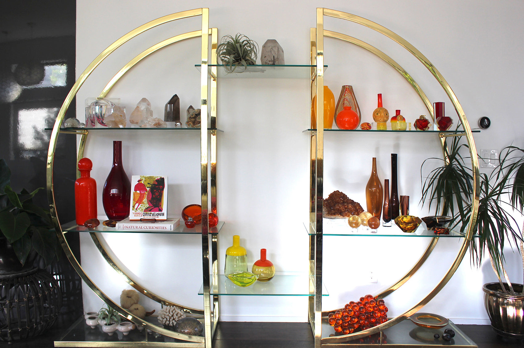 Circular gold structure with glass shelves decorated with crystals and colorful vases.