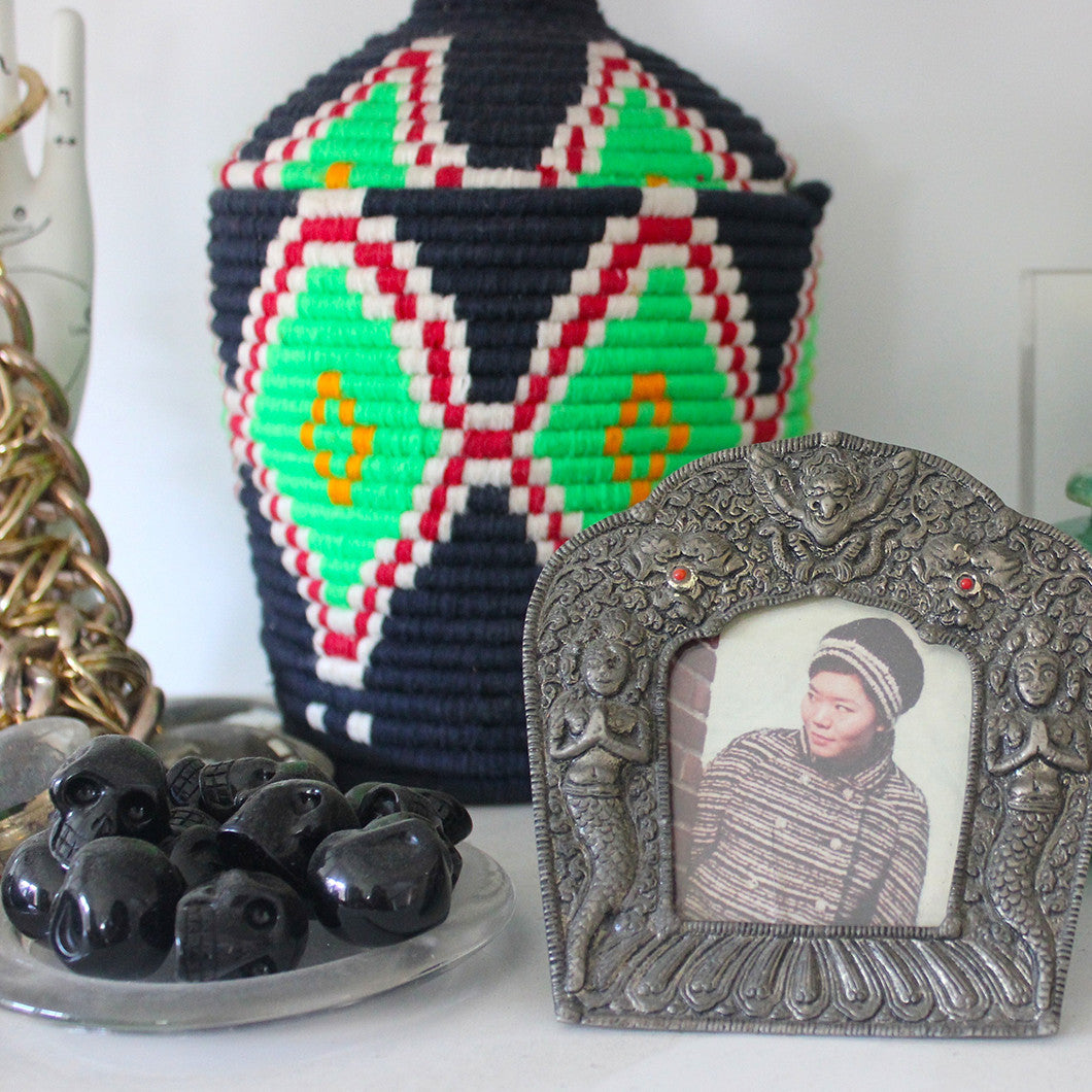 Black stones in the shape of skulls sit next to a framed photo of Rosa's mother.