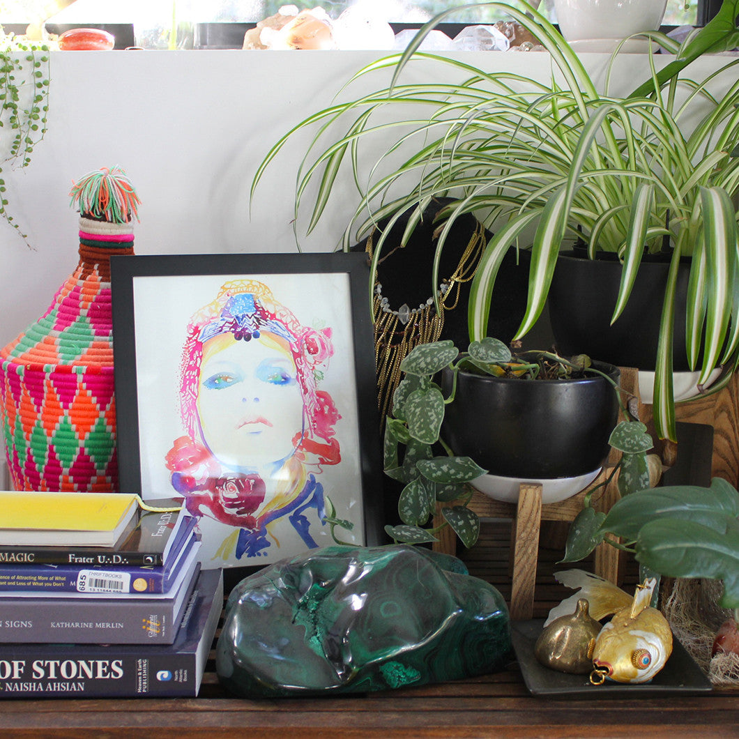 Table with plants, books, a framed painting, and of course, crystals.