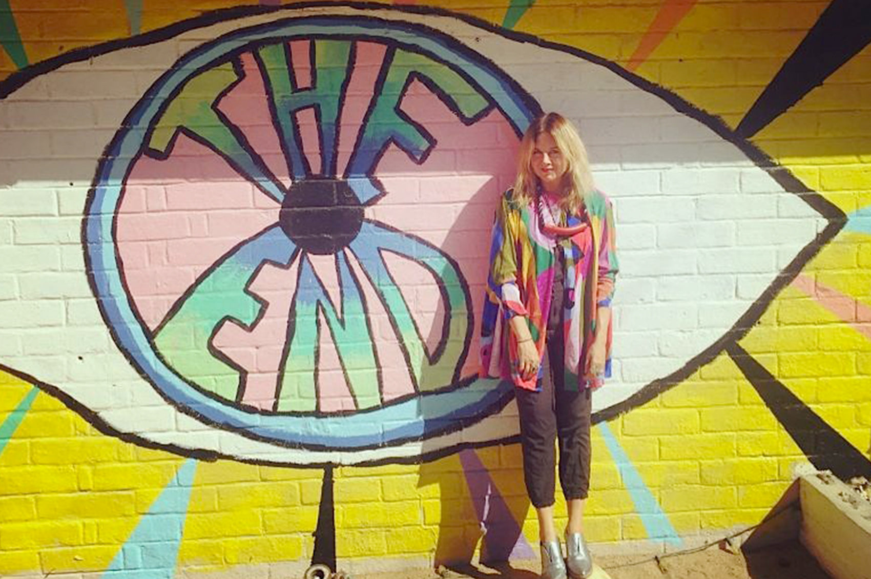 Kime standing in front of her painted The End storefront.