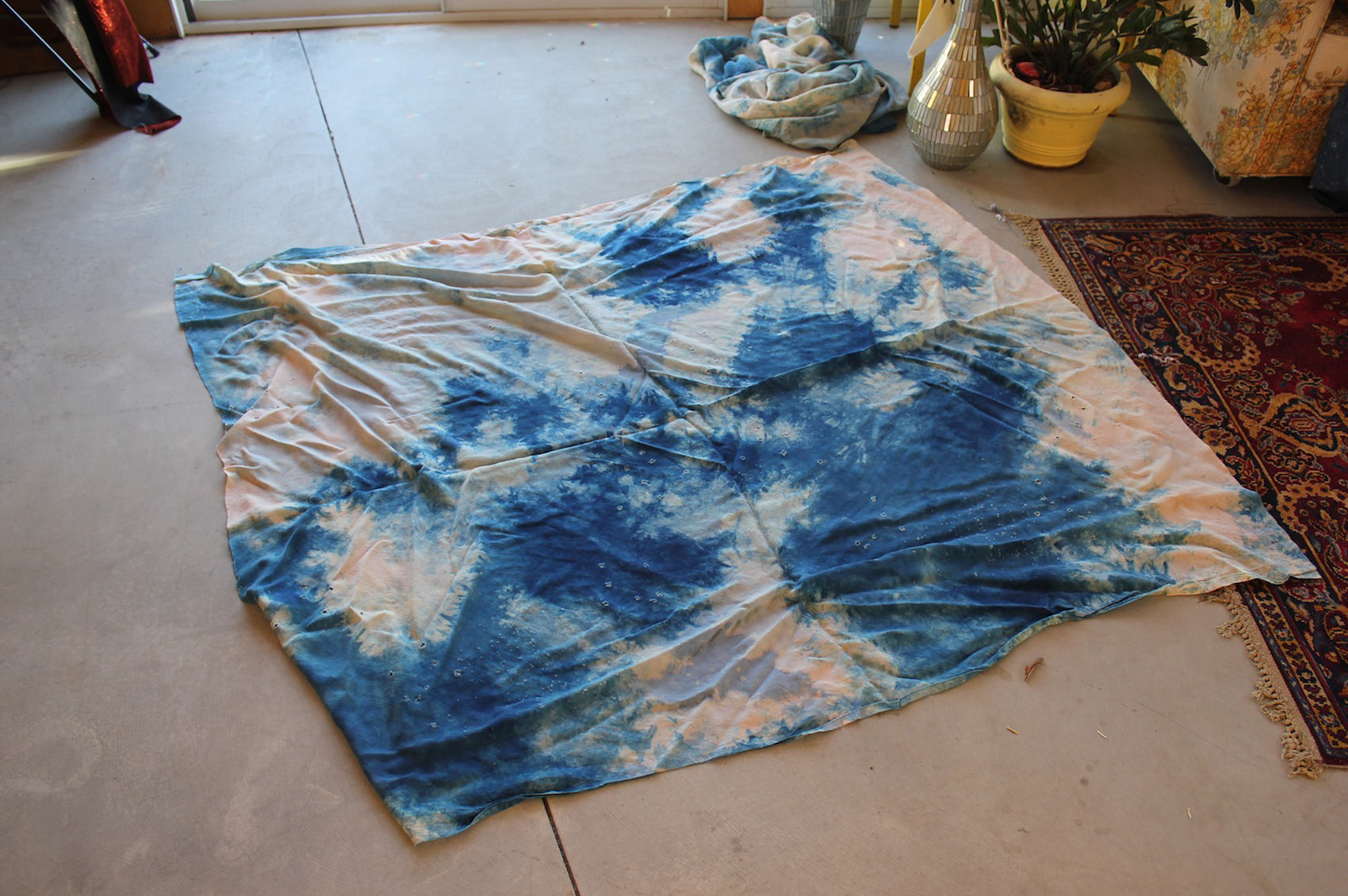 Blue and white tie-dye fabric on the floor of the studio.