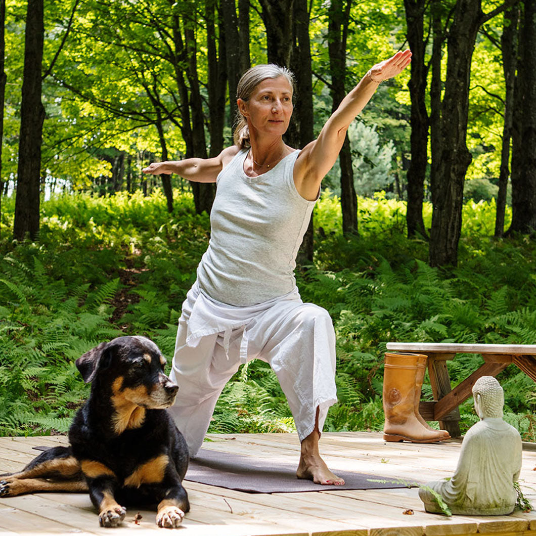 Jeanette practices a yoga pose on a deck with her dog by her side.