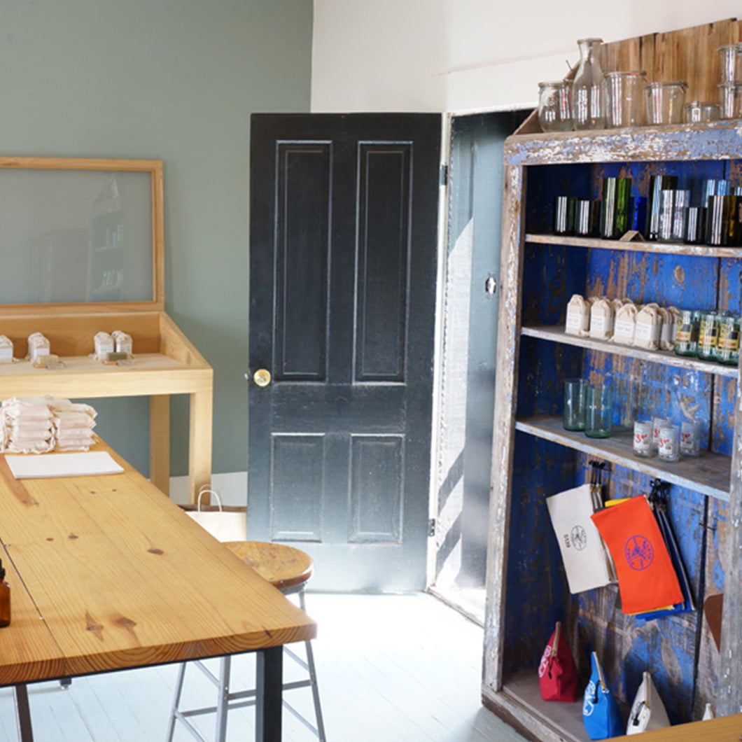 Wooden table and vintage blue cabinet hold soap-making supplies.