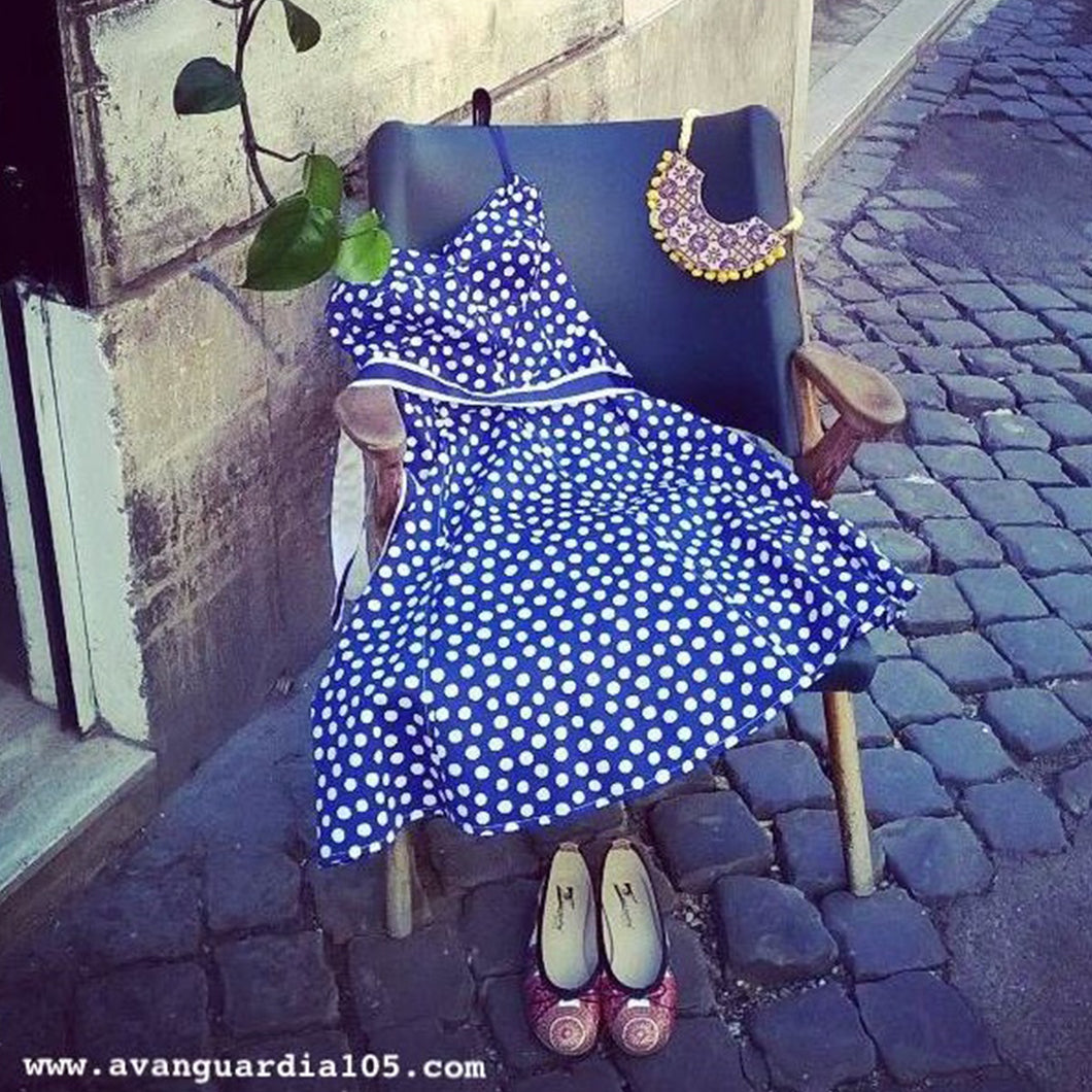 A blue and white polka-dot dress is dislplayed on a chair with shoes and a necklace on a cobblestone street.