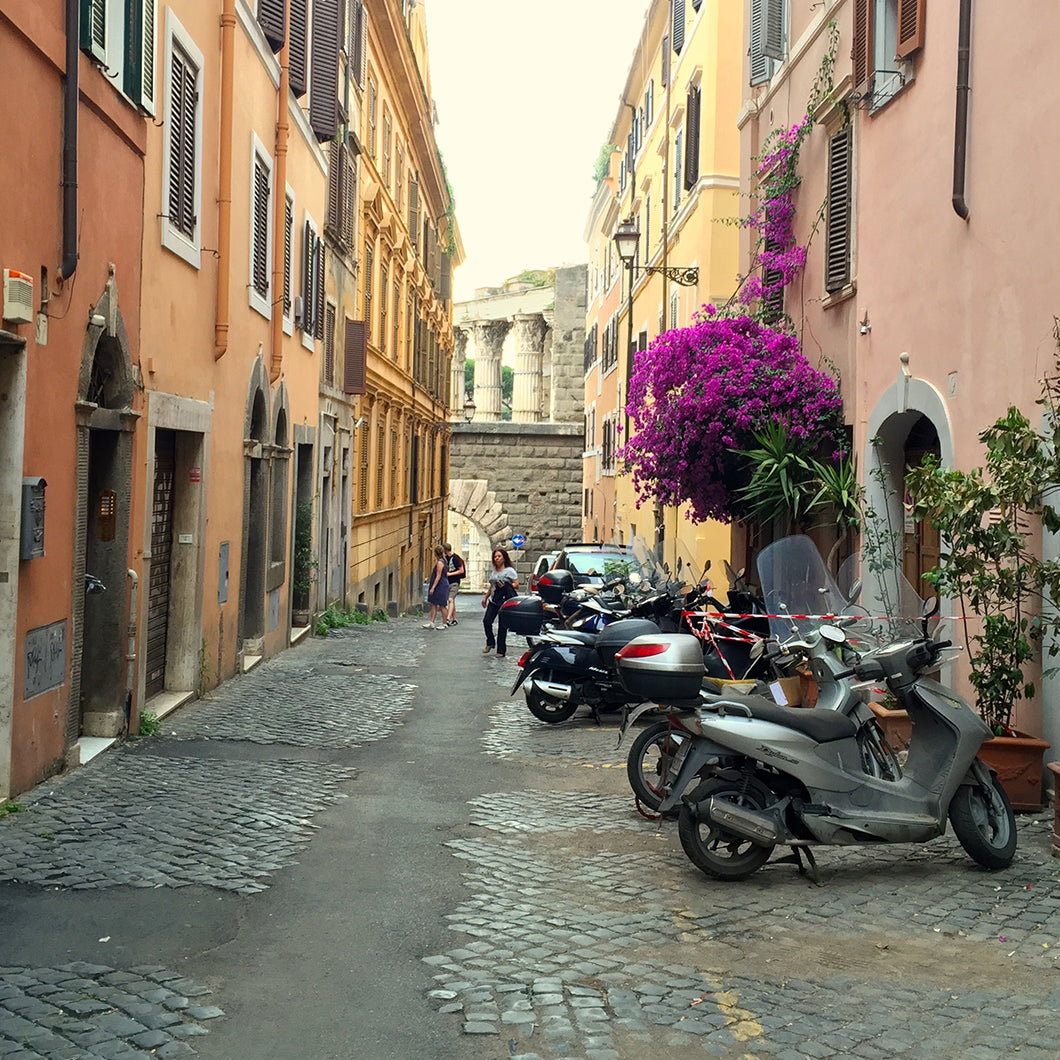 View of Via Baccina's cobblestone street lined with scooters.