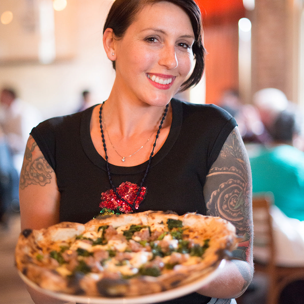 A waitress holds a pizza for a closeup.