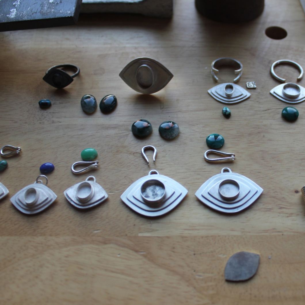Stones and bezels on worktable.