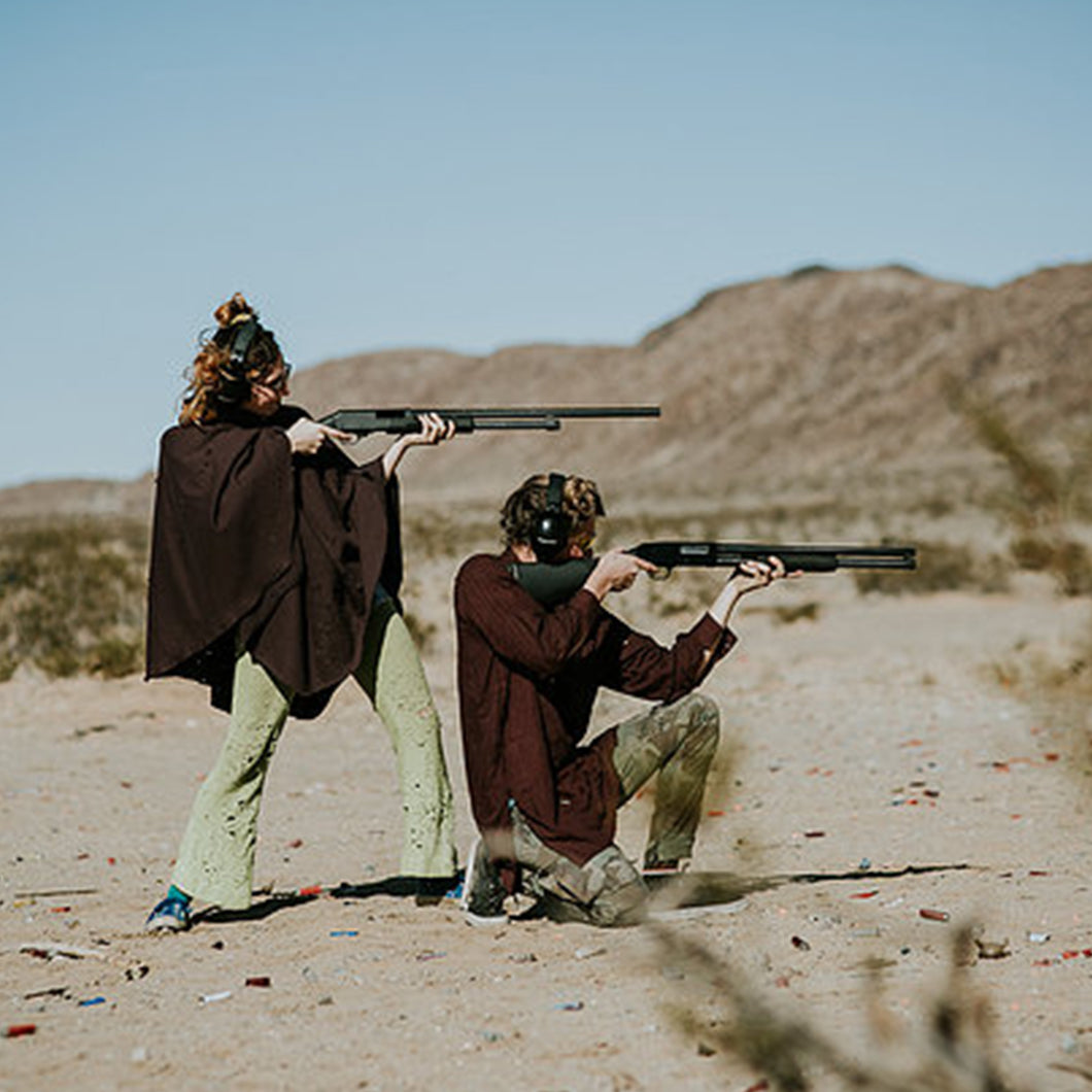 Couple with shotguns in the desert.