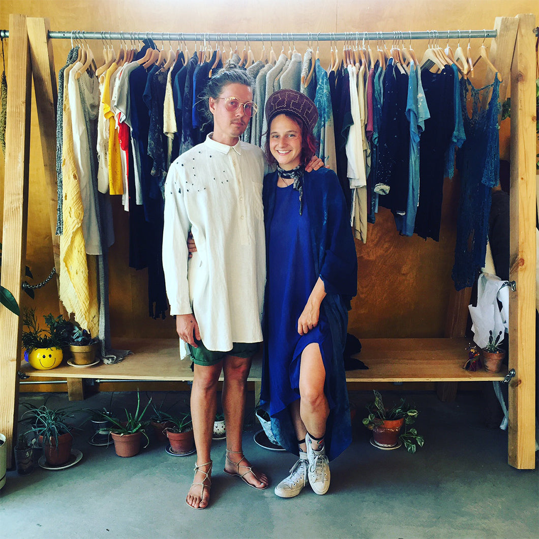 Sarah Harris and Cody Montgomery of TOTALLY BLOWN posing in front of a rack of their clothes.