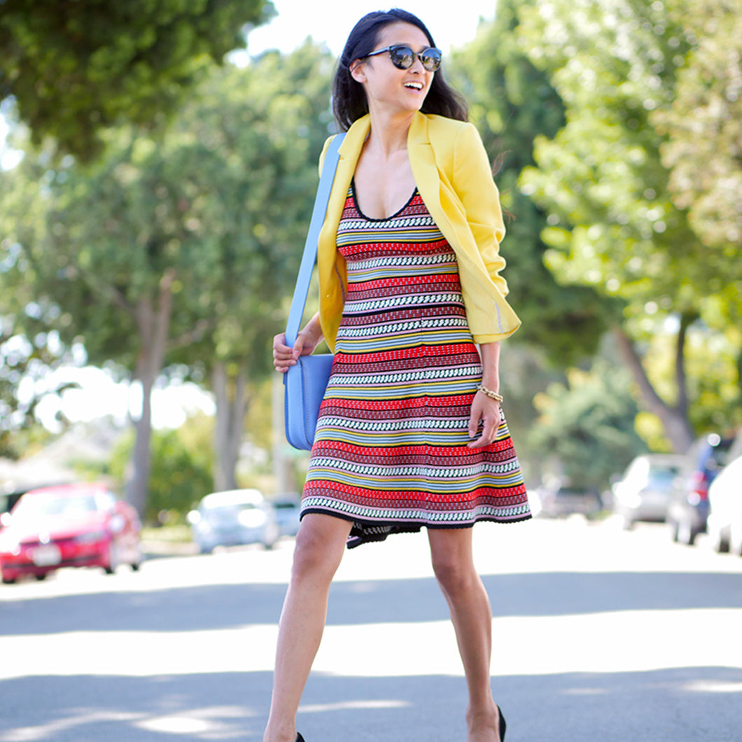 Michelle in a multicolor striped dress with a yellow blazer.