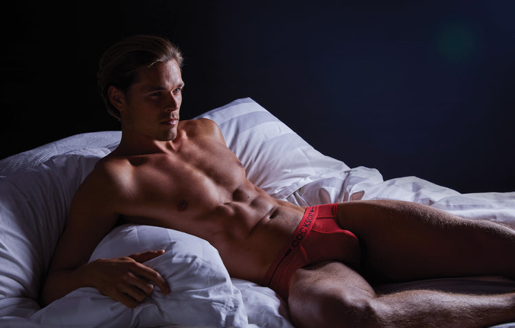 Editorial lifestyle image featuring Cocksox CX76SH sheer underwear sports briefs in Cupid Red