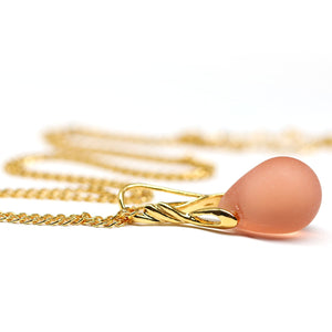 Frosted peach drop glass pendant on golden coated chain