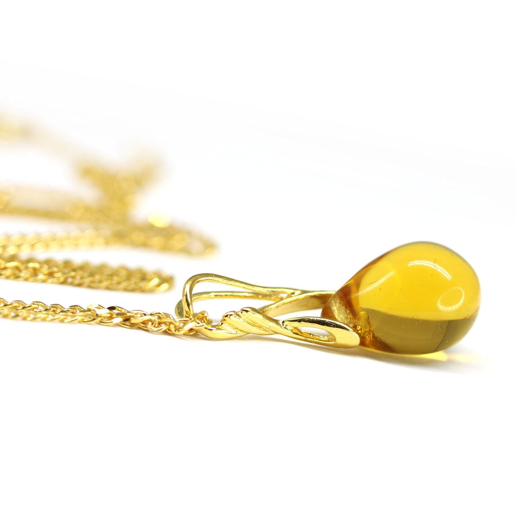 Amber yellow drop glass pendant on golden coated chain