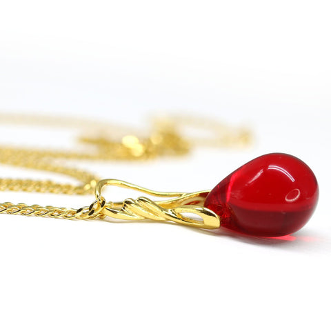 Red drop glass pendant on golden coated chain