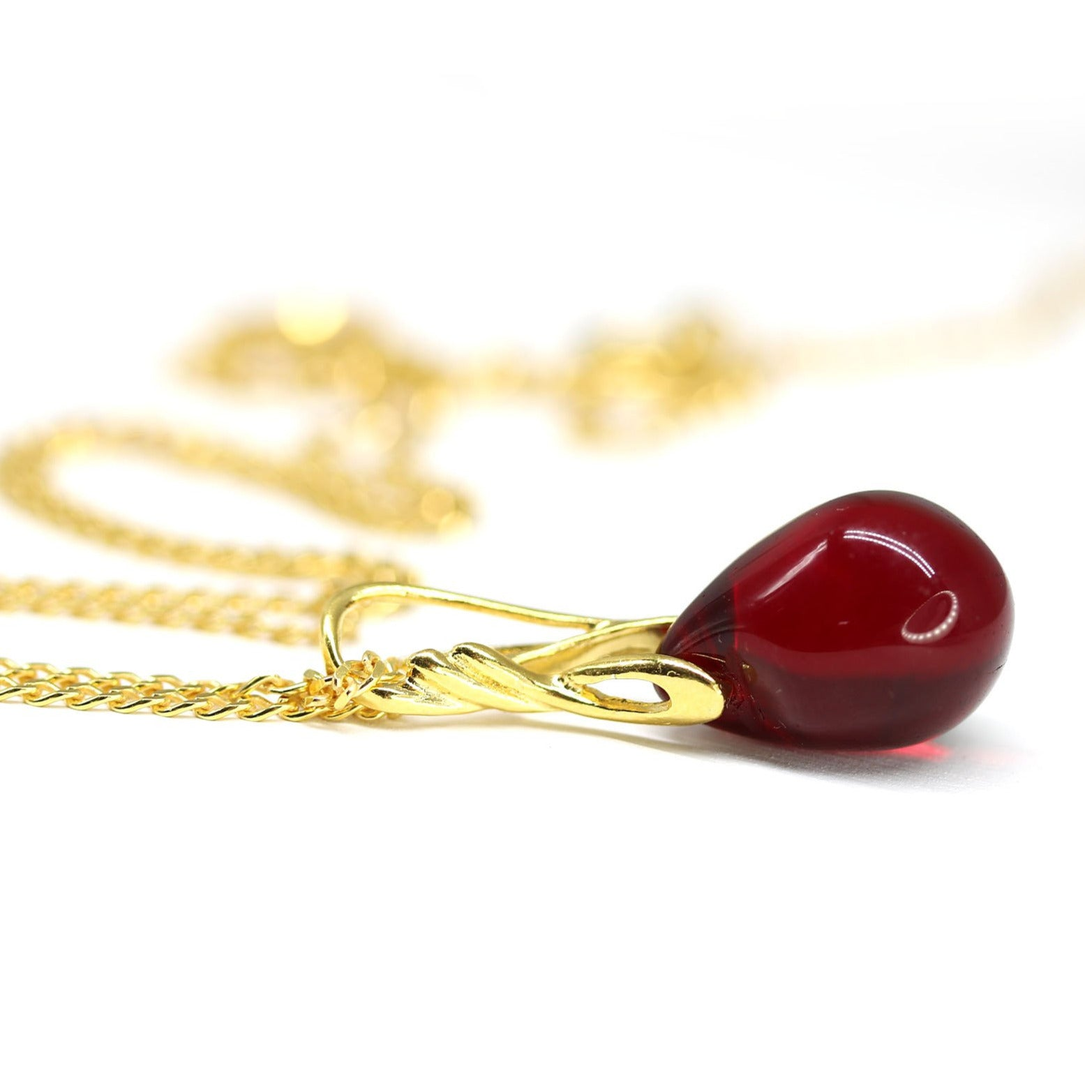 Dark red drop glass pendant on golden coated chain