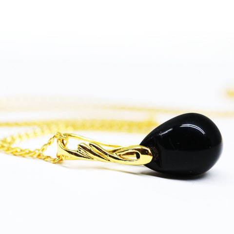 Black drop glass pendant on golden coated chain