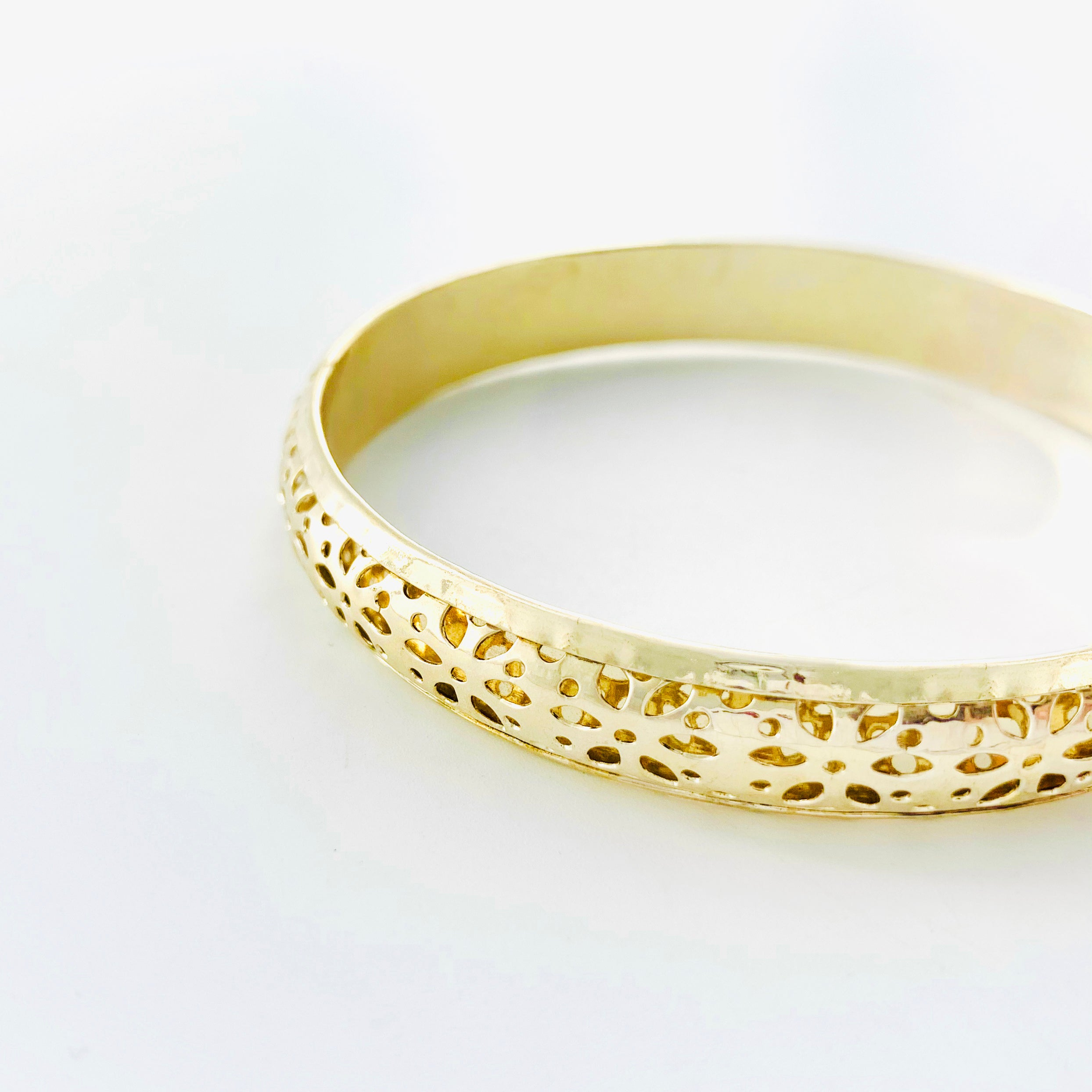 Gold bangle with floral cut-out patterns