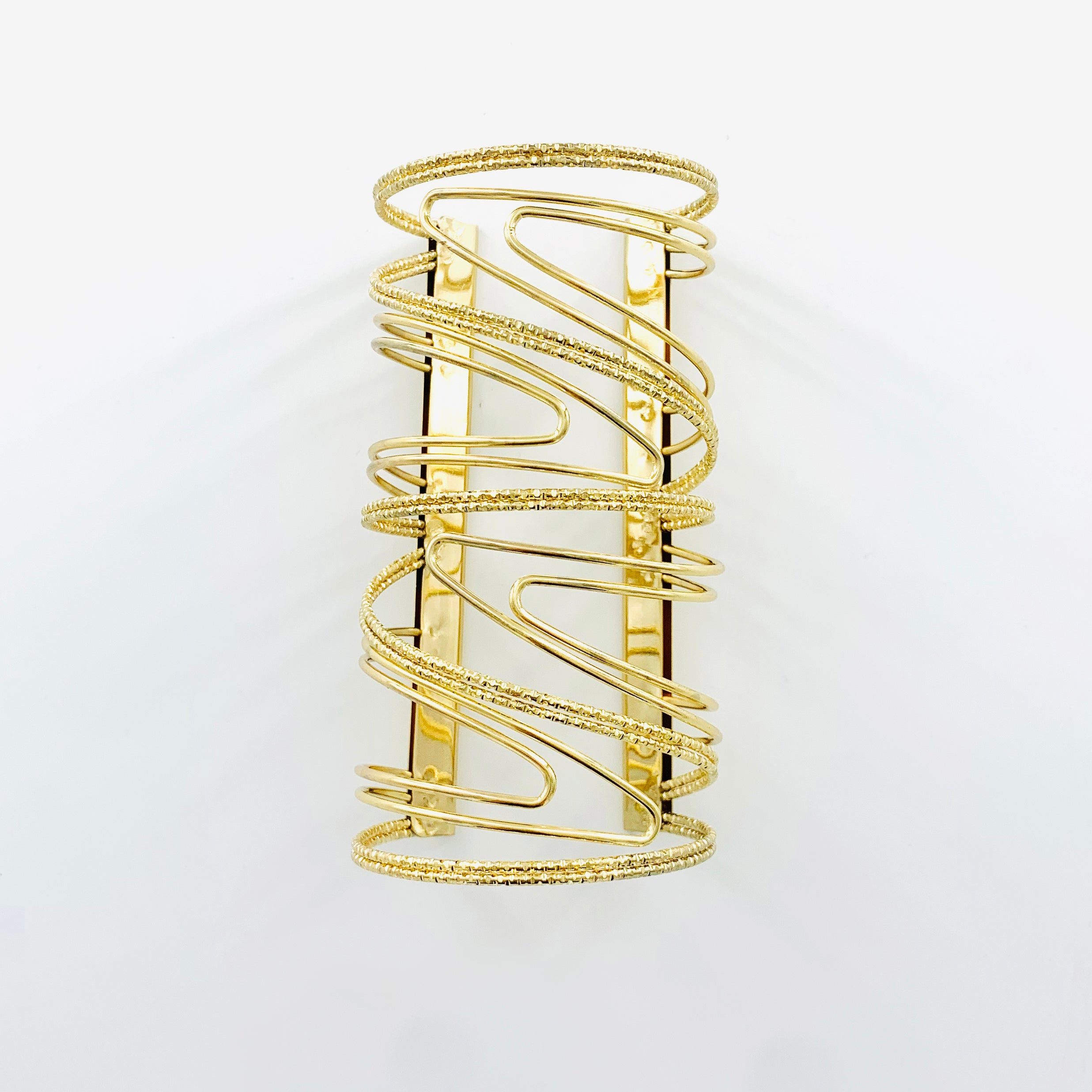 Wide cuff with wavy design in Gold