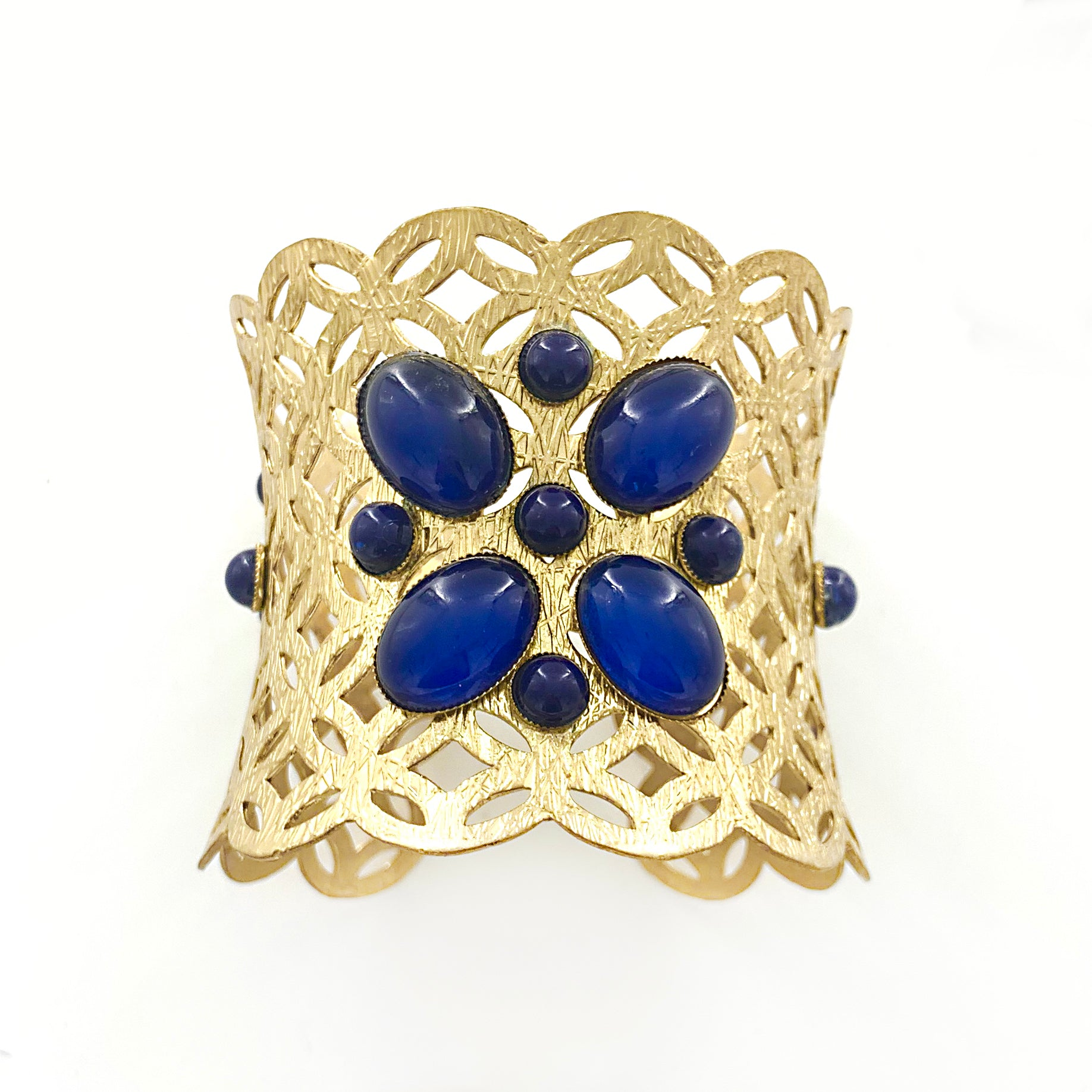 Matt gold cuff with geometric cut-outs and blue beads