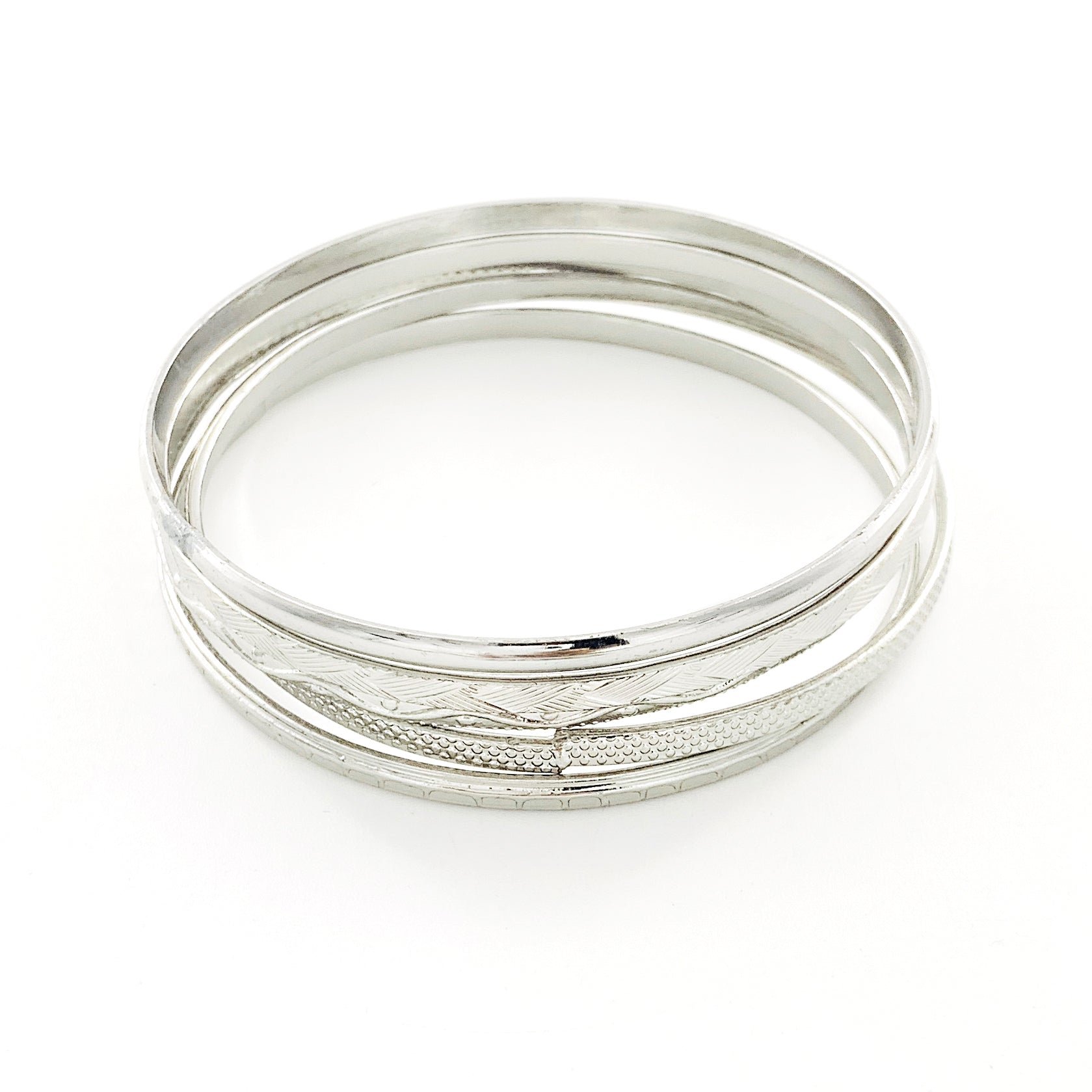 Thin silver bangles with textured patterns