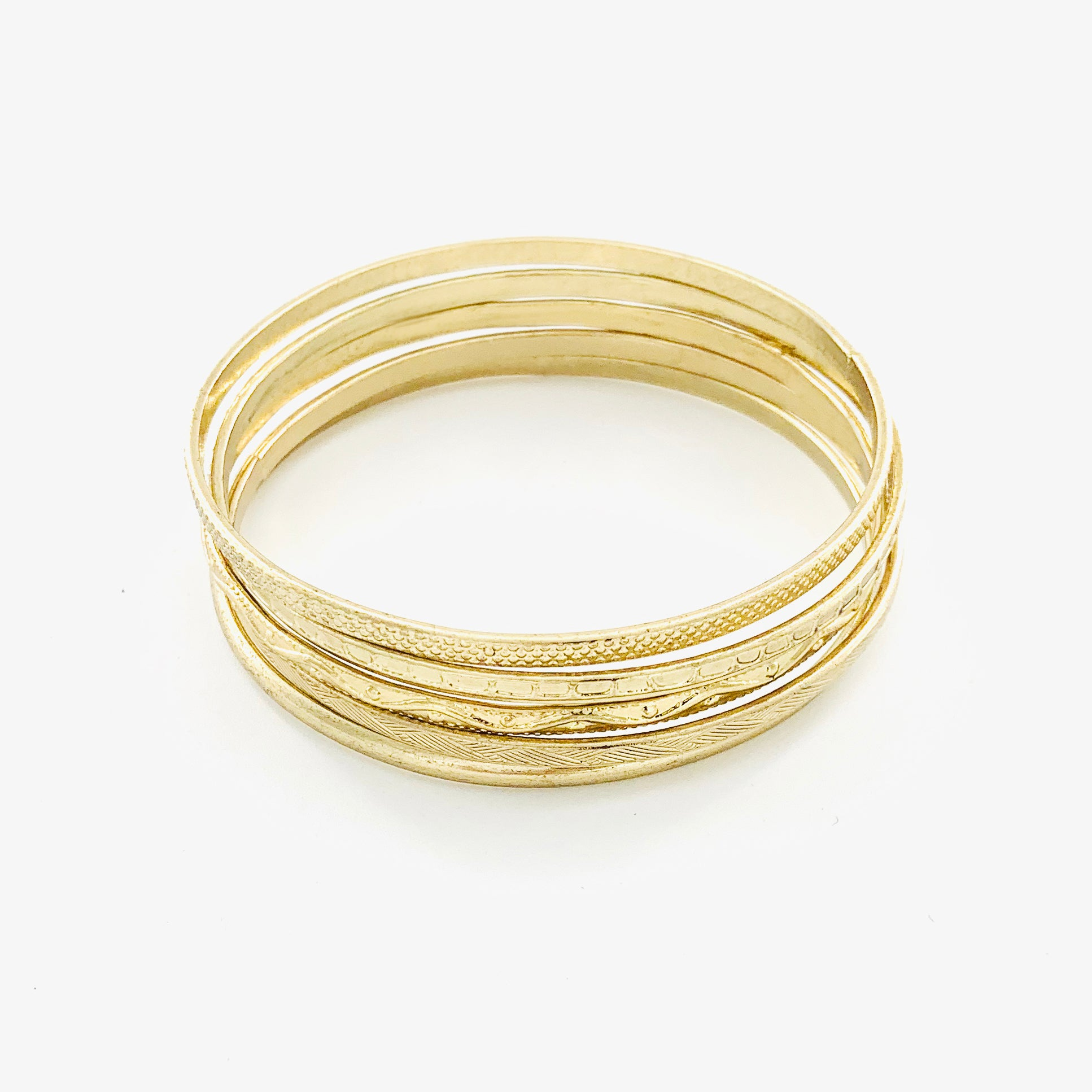 Thin gold bangles with textured patterns