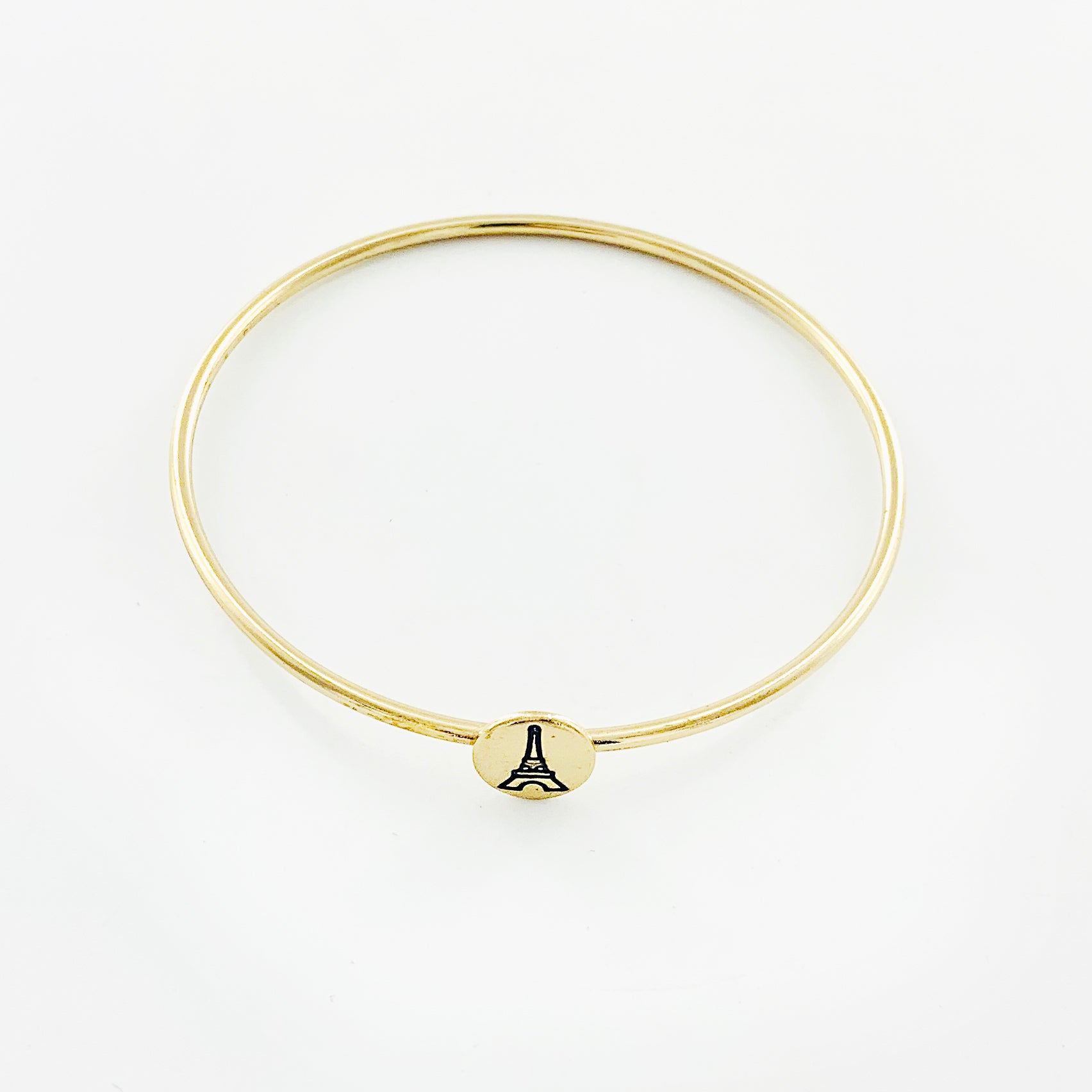 Thin gold bangle with engraved Eiffel Tower disc