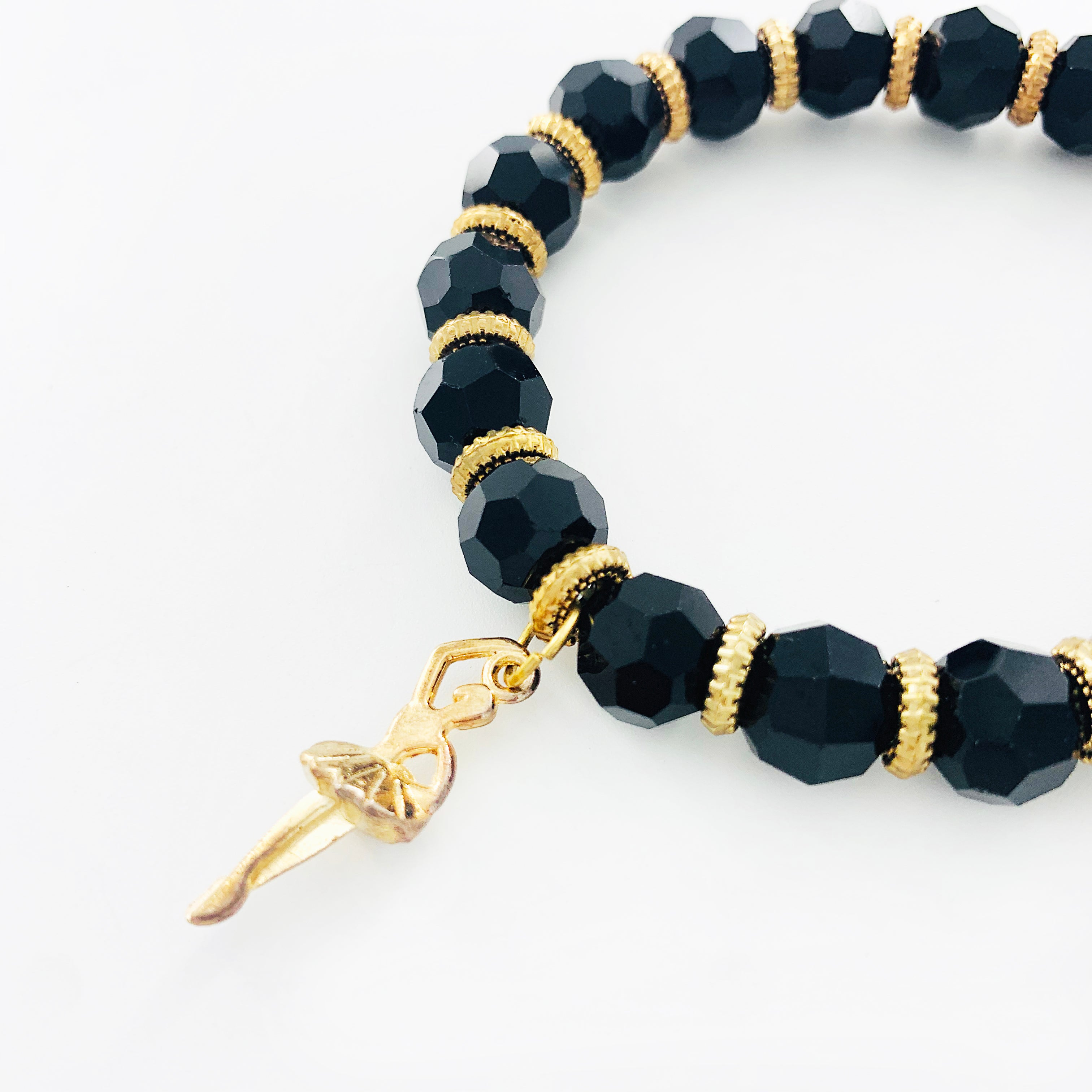 Black faceted glass beads with gold ballerina charm