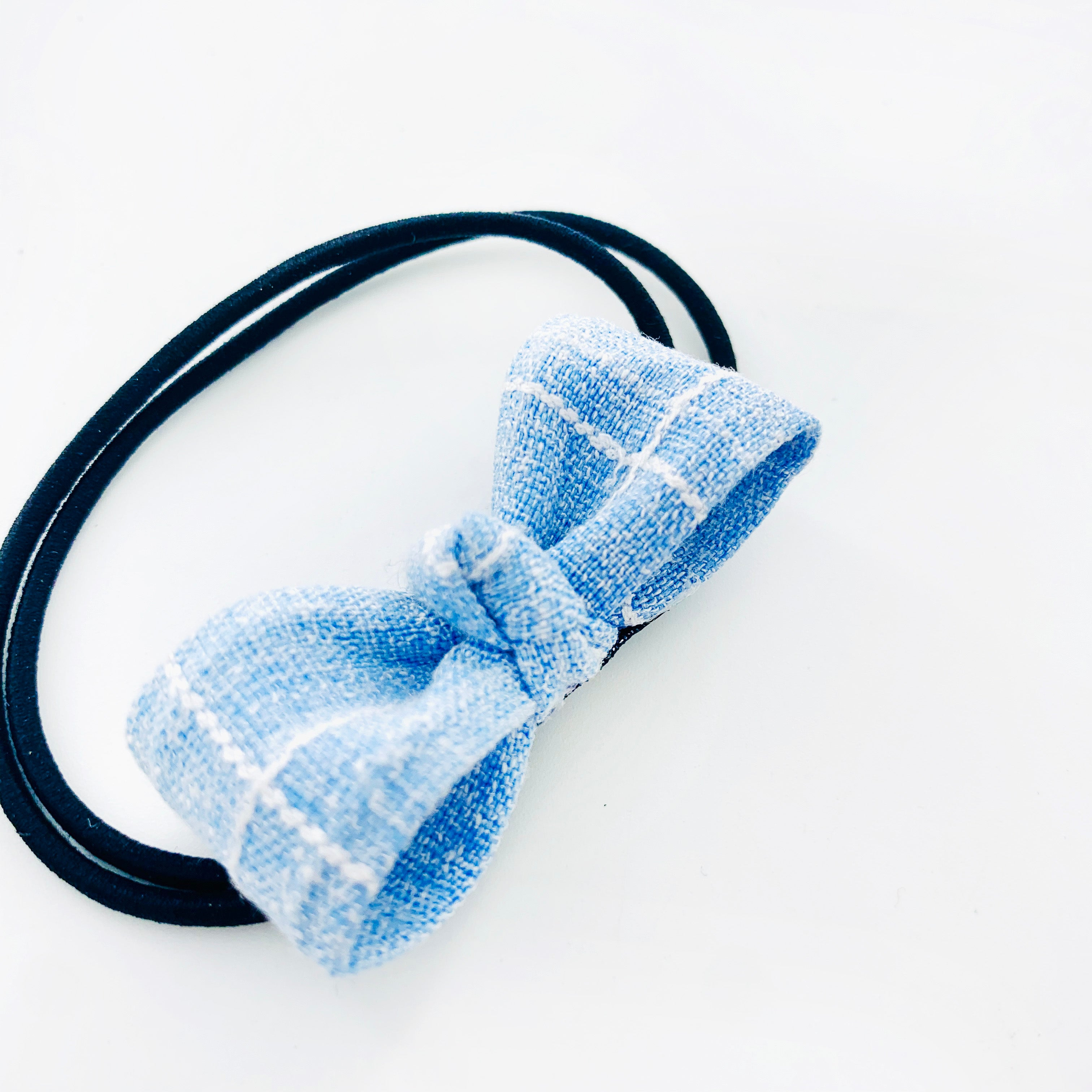 Hair tie with small blue fabric ribbon