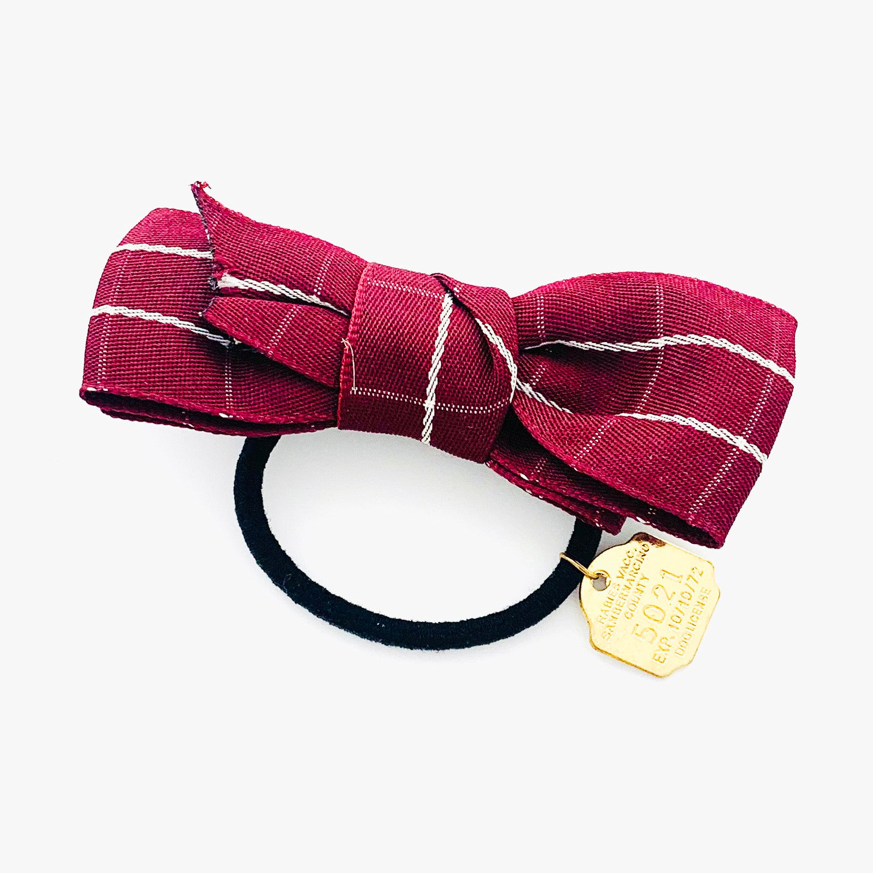 Hair tie with maroon fabric ribbon and gold charm detail