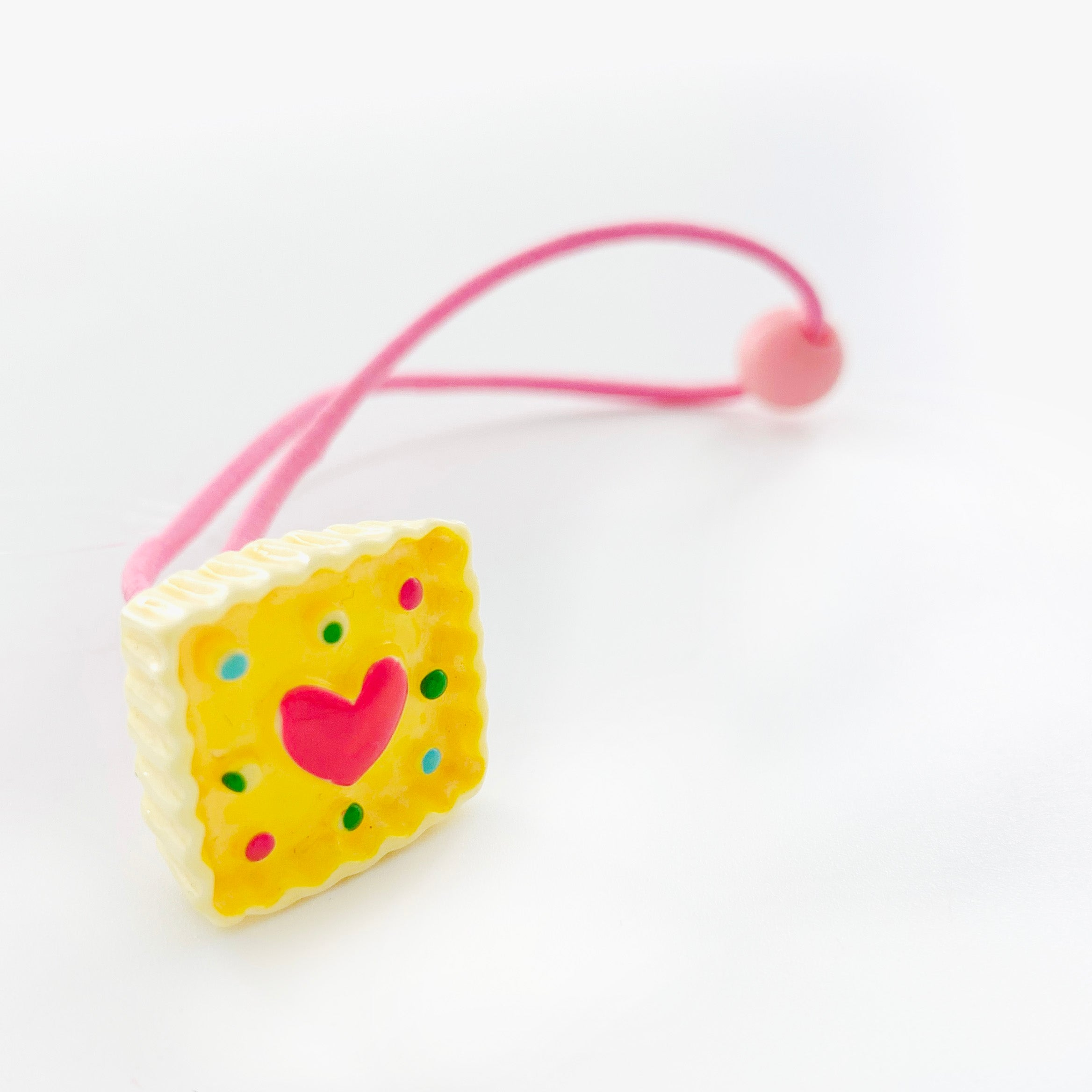 Pink rubber band with yellow cake