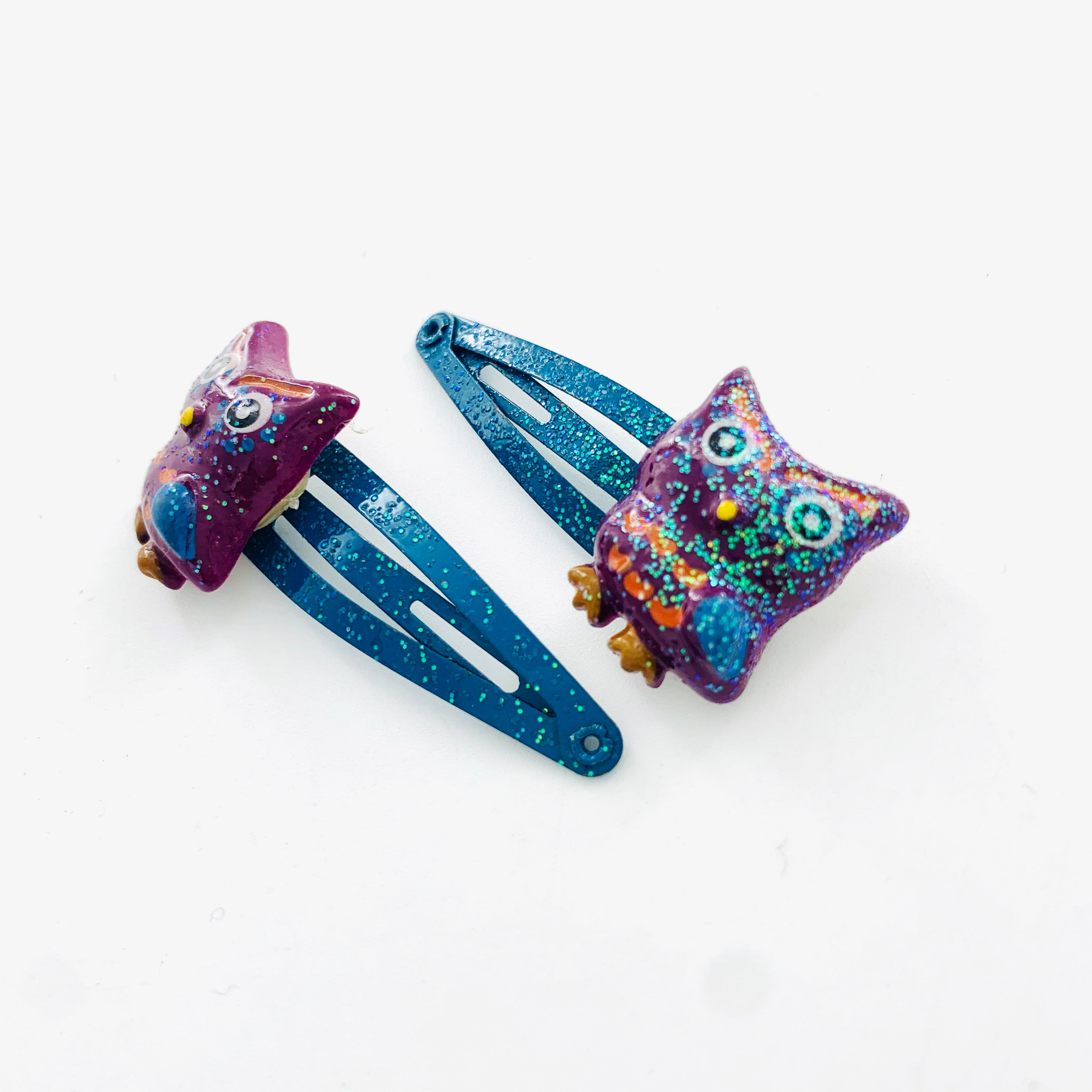A pair of hair clips with owls and glitter finish