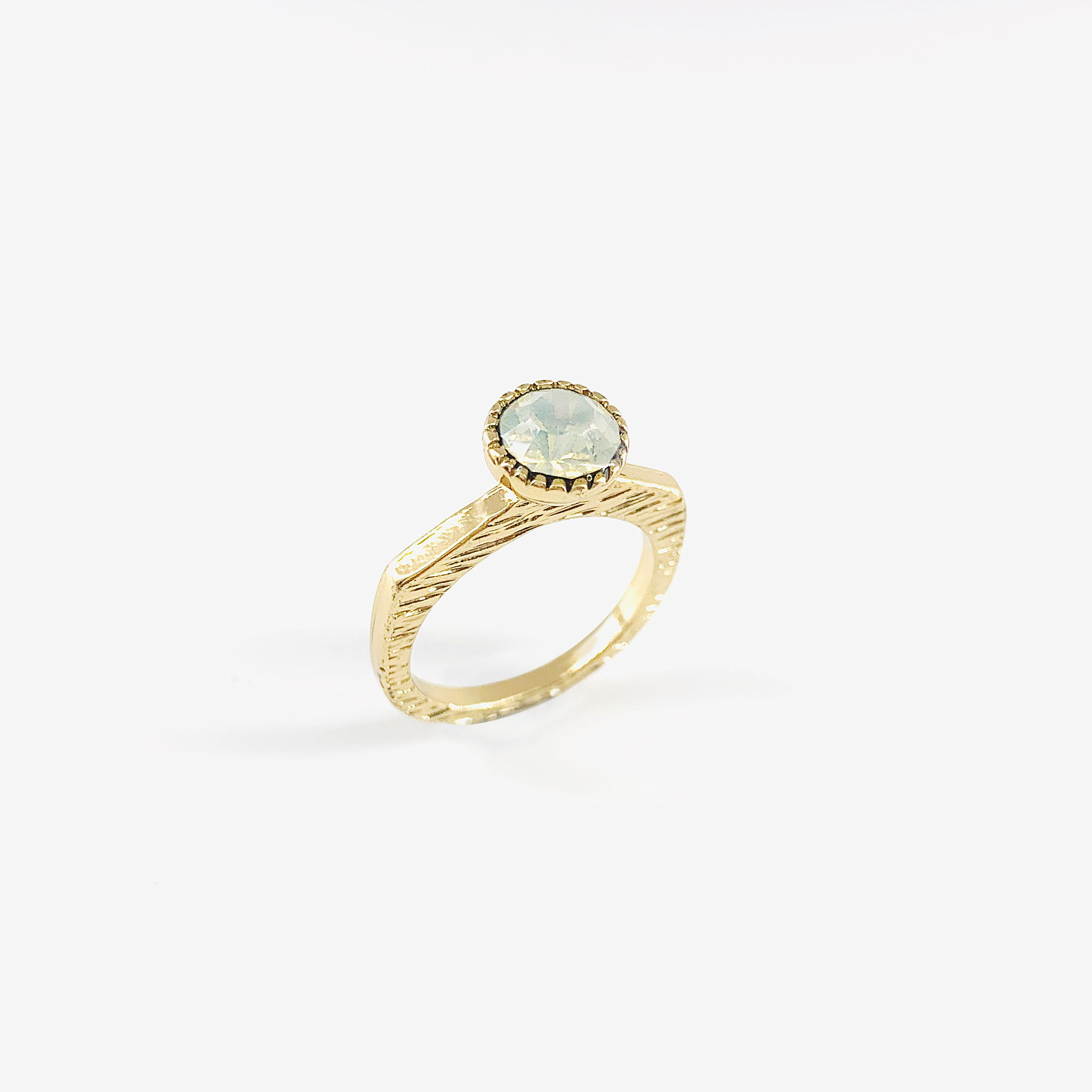 Textured gold ring with white stone