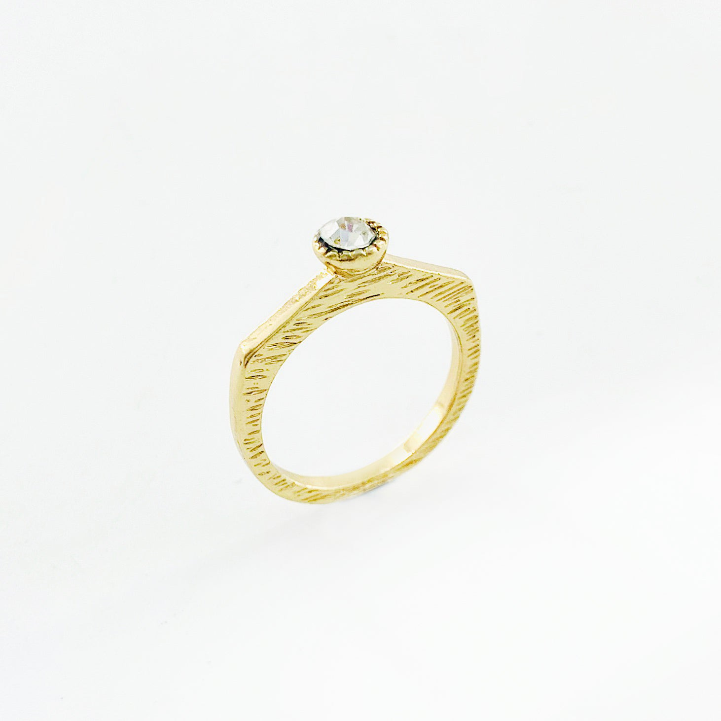Textured gold ring with small white stone