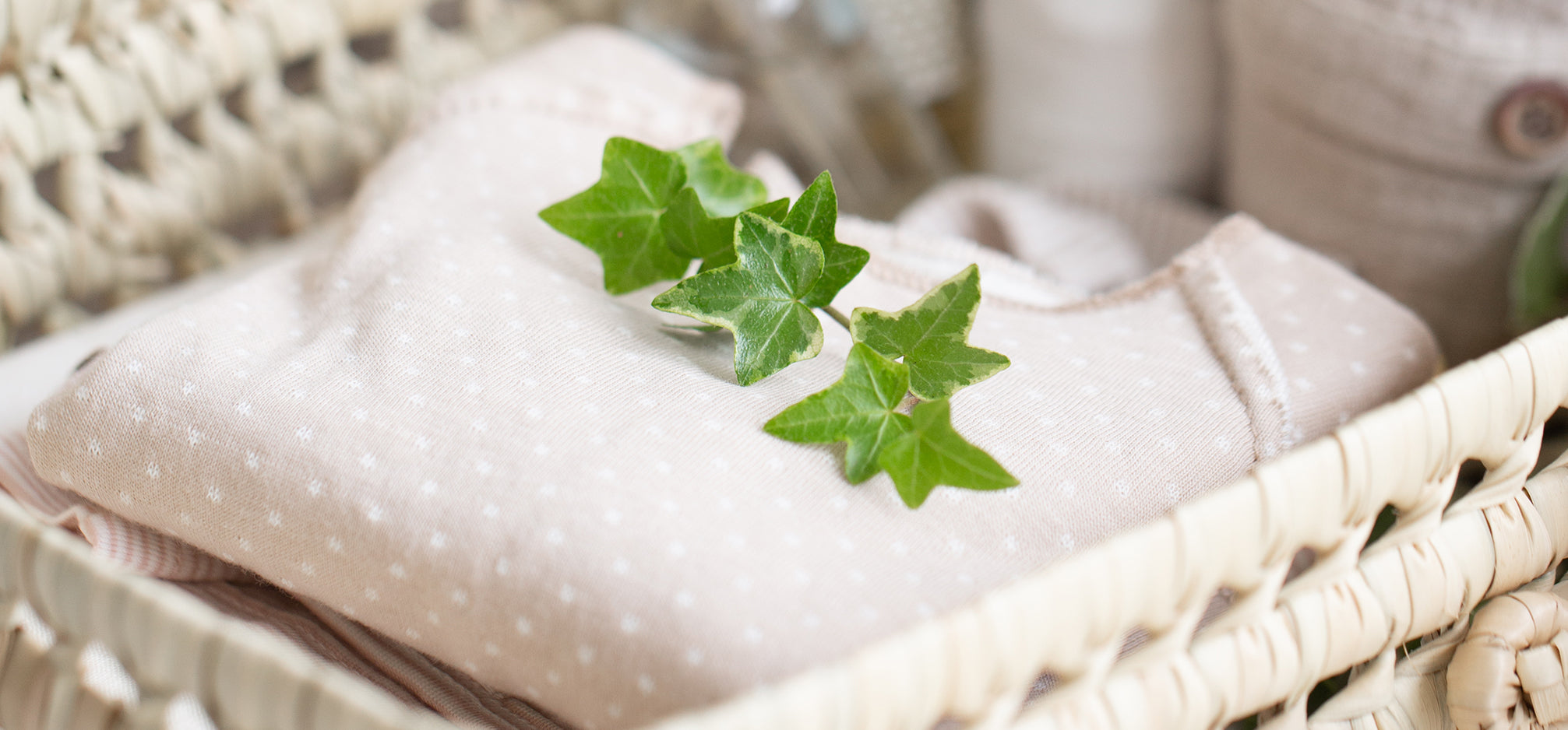 Baby clothing folded in a basket with a leaf on top.