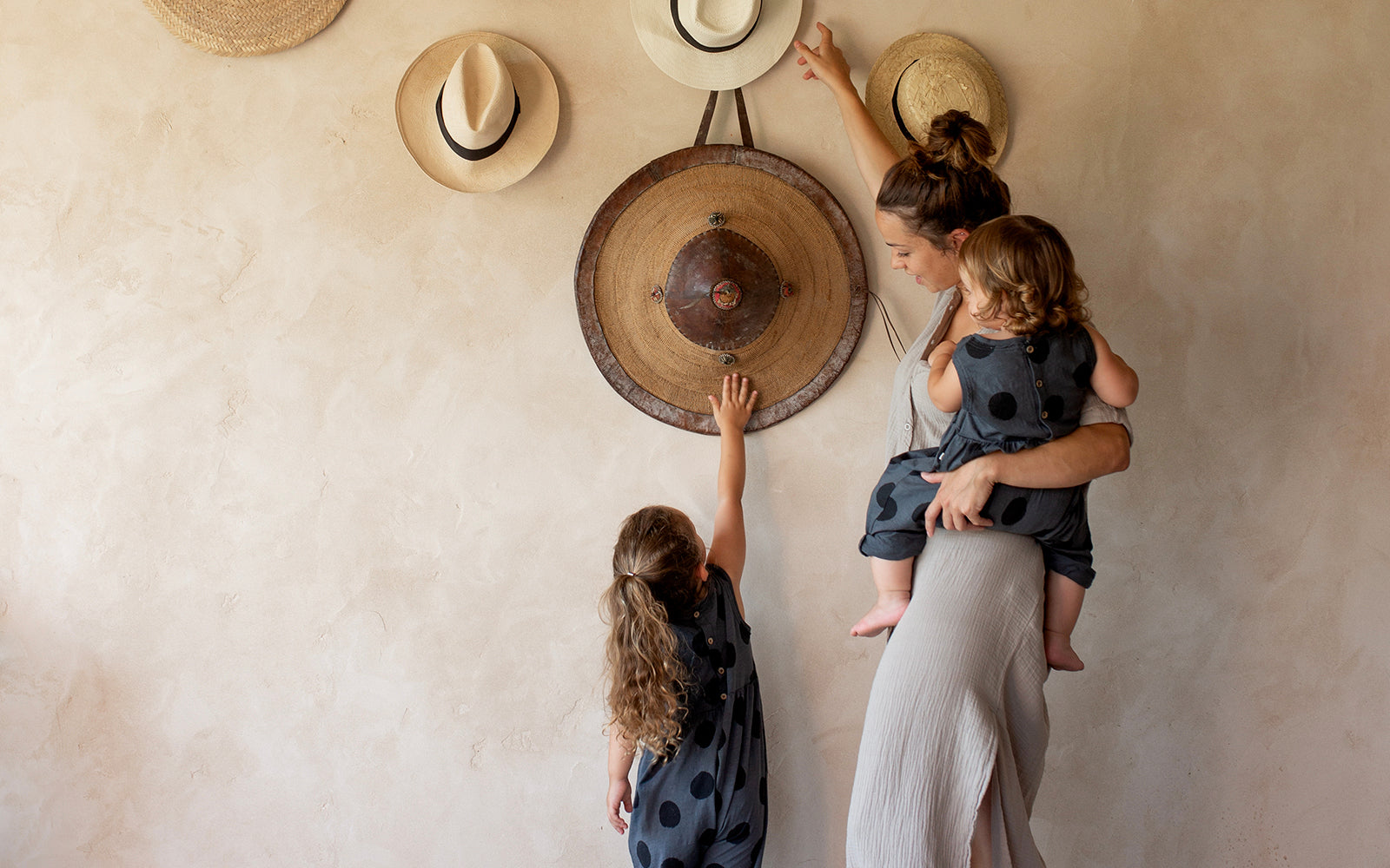 Girl reaching for some hats hanging on a wall with her mother.