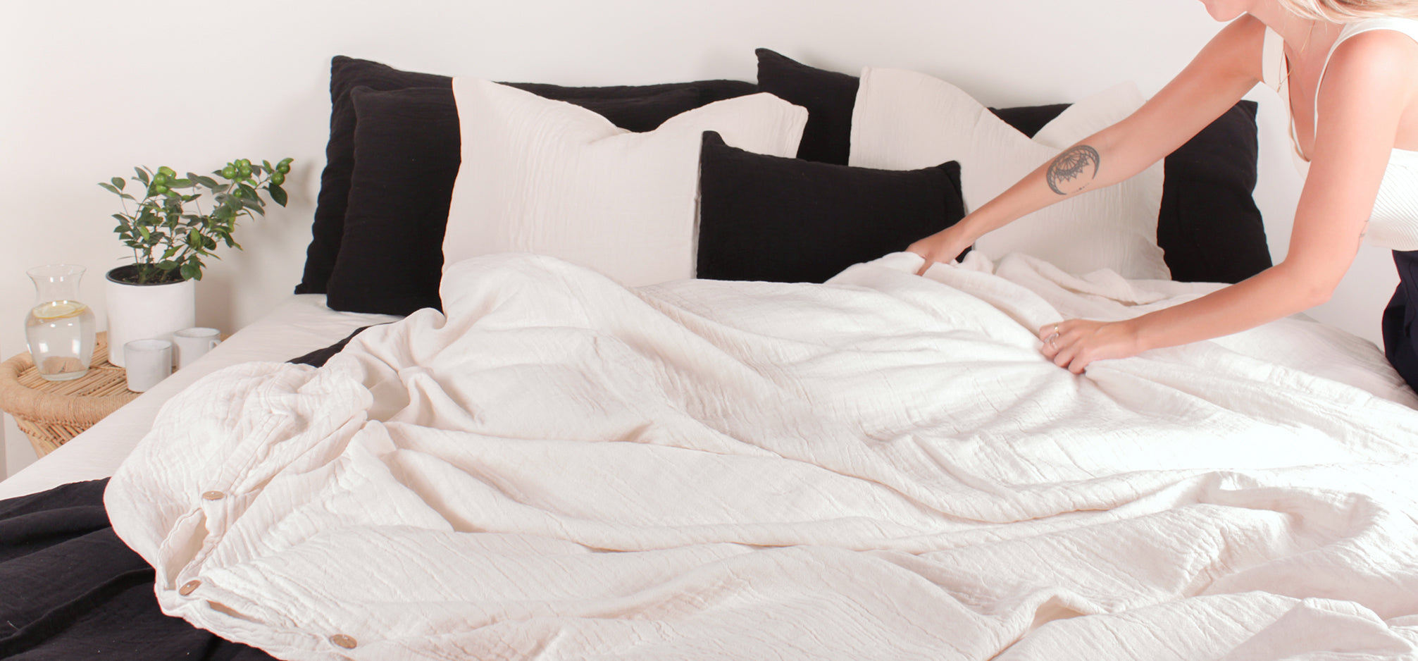 A woman making a bed with black and white bed linens.